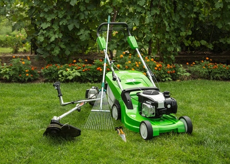 26072069 - green lawnmower, weed trimmer, rake and secateurs in the garden. Copyright: <a href='https://www.123rf.com/profile_vitalliy'>vitalliy / 123RF Stock Photo</a>
