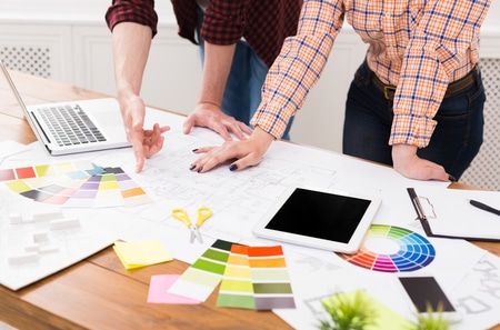 professional designers team working on project, discussing functional space creation, decoration ideas, choosing color scheme