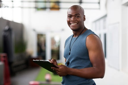 34093482 - handsome male personal trainer with clipboard