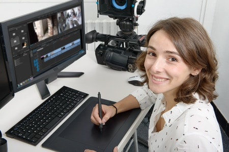 67141376 - young woman designer using graphics tablet for video editing